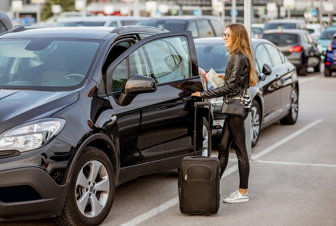 Woman getting into a rental car.