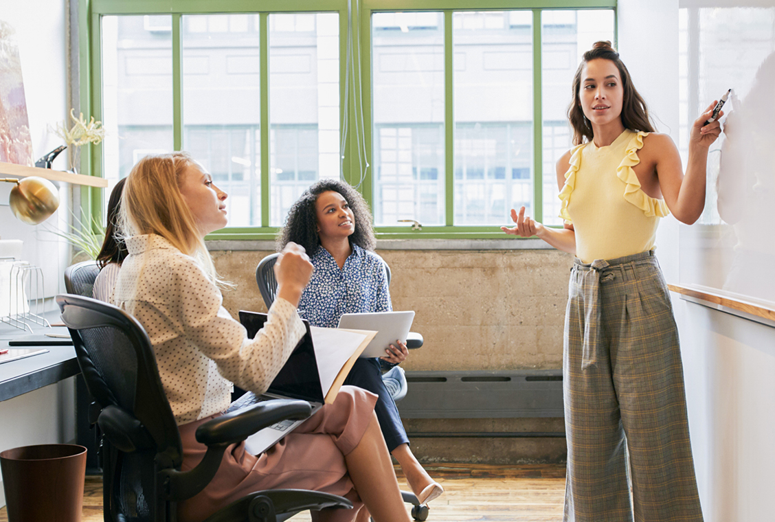 Woman looking to whiteboard in a meeting with a diverse female team.