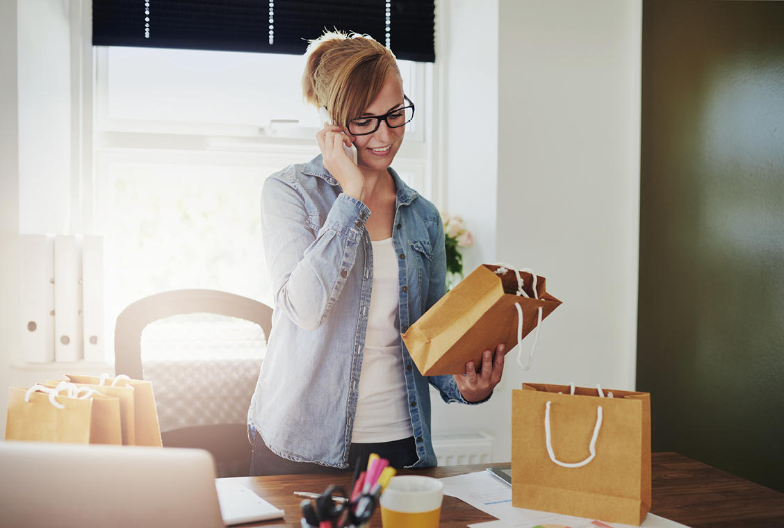 blonde woman in a ponytail, black glasses and a denim shirt on the phone while looking at a brown bag in her hand in her home office.