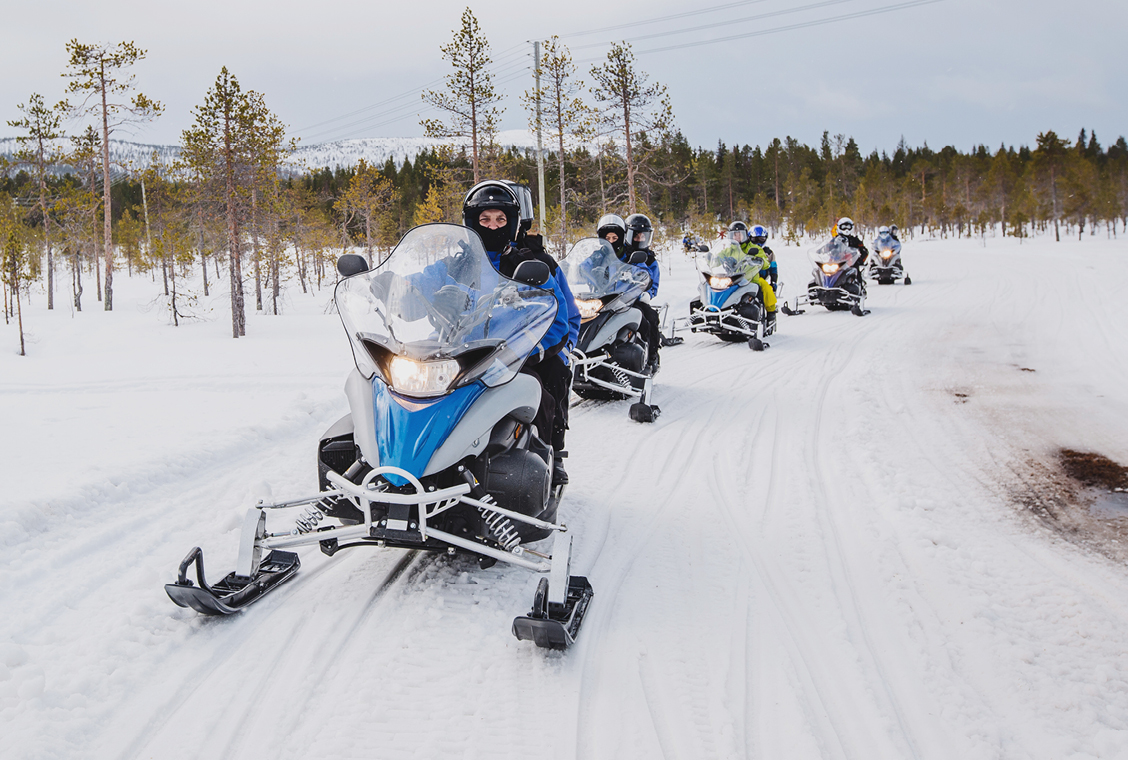 Five snowmobiles with family members riding them drive down a snowy prairie trail in a row.