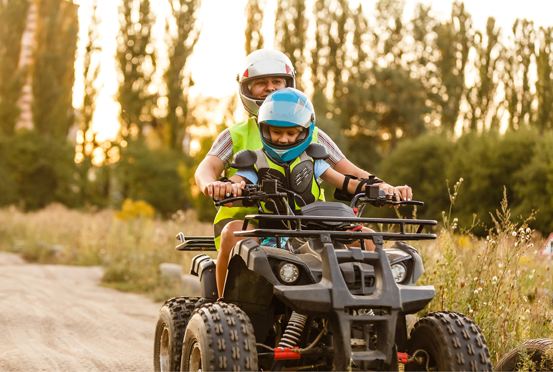 Father and son ride quad down dirt path outside.
