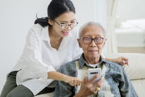 Elderly man using a phone with his daughter.
